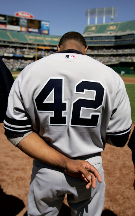 New York Yankees' Robinson Cano bows his head during the national anthem as he wears the #42 jersey of Jackie Robinson Sunday, April 15, 2007, prior to the baseball game with the Oakland Athletics in Oakland, Calif. Players around the country honored Robinson in recognition of the 60th anniversary of the day Jackie Robinson put on a Brooklyn Dodgers uniform in a regular-season game for the first time. (AP Photo/Ben Margot)