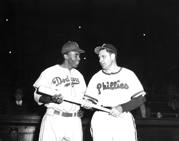 Jackie Robinson, left, Brooklyn Dodgers' first baseman, looks over the bat Philadelphia Phillies manager Ben Chapman uses during practice, as he prepared to play his first Philadelphia game for the Dodgers on May 9, 1947. (AP Photo)
