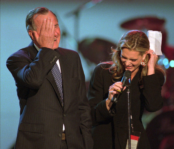 Former President George Bush, left, horses around on stage with actress Brooke Shields Agassi during the President's Service Awards Sunday, April 27, 1997, in Philadelphia. The two began playing around after the teleprompter stopped working causing them to ad-lib a little. (AP Photo/Chris Gardner)