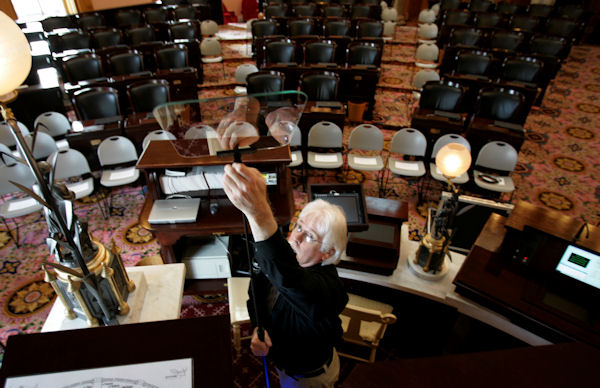 Tom Burns adjusts a teleprompter glass by the podium in the House chamber Tuesday, March 13, 2007, in Columbus, Ohio, as he prepares for Gov. Ted Strickland's State of the State address on Wednesday. (AP Photo/Kiichiro Sato)