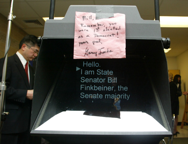 A note taped on a Teleprompter written by Washington Gov. Gary Locke, back left, waits as a joke for State Sen. Bill Finkbiener, R-Kirkland, for his rebuttal to Locke's State of the State Address at Olympia High School in Olympia, Wash. Tuesday, Jan. 13 2004. (AP Photo/John Froschauer)