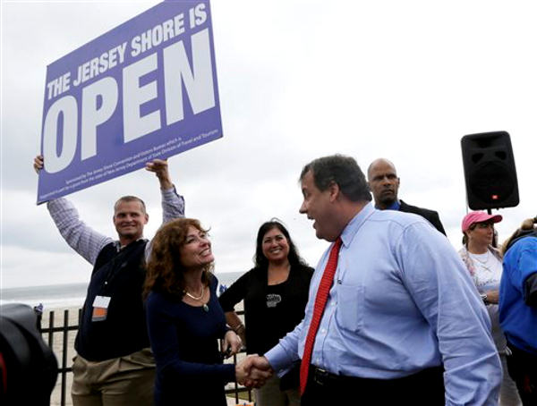 New Jersey Gov. Chris Christie, right, talks to Carla Pilla, of Seaside Heights, N.J., while Robert Hilton, left, executive director of the Jersey Shore Convention and Visitor's Bureau, holds a sign, Friday, May 24, 2013, in Seaside Heights, N.J. Christie cut a ribbon to symbolically reopen the state's shore for the summer season, seven months after being devastated by Superstorm Sandy. Several beach communities have annual beach ribbon cuttings, announcing they are back in business. But this year's ceremonies are more poignant seven months after a storm that did an estimated $37 billion of damage in the state. (AP Photo/Julio Cortez)