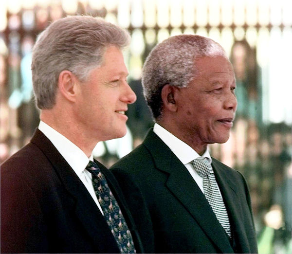 "President Clinton stands with South African President Nelson Mandela during the official arrival ceremony in Cape Town, South Africa, Thursday, March 26, 1998. Proudly becoming the first U.S. head of state to visit this onetime pariah nation, President Clinton called for a partnership ""of mutual respect and mutual reward'' with the new South Africa. (AP Photo/J. Scott Applewhite)"