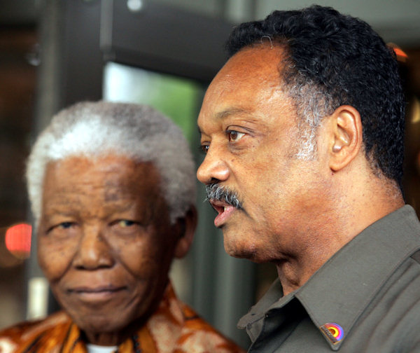 American Rev. Jesse Jackson, right, speaks to journalist as former South African president Nelson Mandela, left, looks on after their meeting in Johannesburg, South Africa, Wednesday, Oct. 26, 2005. (AP Photo/Themba Hadebe)