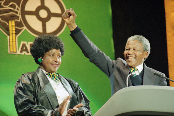 South African anti-apartheid leader Nelson Mandela with his wife Winnie at his side, raises his fist as he acknowledges the cheers of thousands at a rock concert Monday, April 16, 1990 at London's Wembley Stadium. (AP Photo/Martin Cleaver)