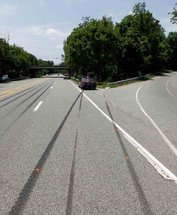 A police car sits near skid marks leading to the scene of an auto accident Monday, June 20, 2011, in West Chester, Pa. West Goshen Township police say Jackass cast member Ryan Dunn and a passenger died after his car left the roadway and burst into flames. (AP Photo/Matt Rourke)