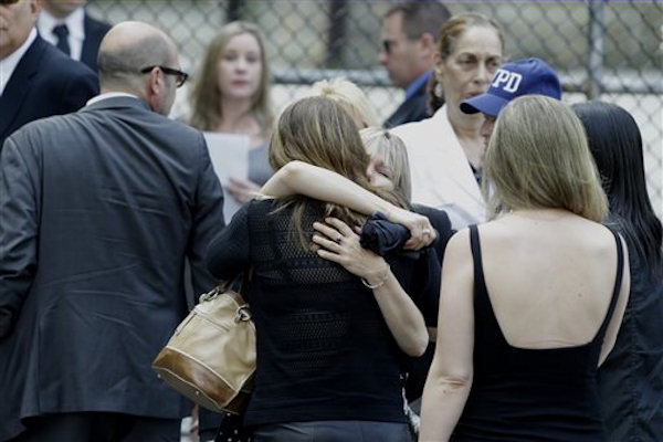 "Women embrace outside of Cathedral Church of Saint John the Divine before funeral services actor James Gandolfini, Thursday, June 27, 2013, in New York. Gandolfini, who played Tony Soprano in the HBO show ""The Sopranos"", died while vacationing in Italy last week. (AP Photo/Julio Cortez)"