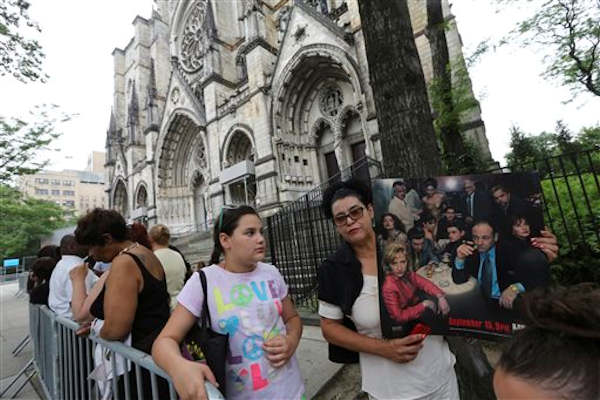 "Stephanie Solano, right, and her daughter Sophia wait in line outside Cathedral Church of Saint John the Divine ahead of the funeral service for James Gandolfini, Thursday, June 27, 2013 in New York. Gandolfini, who played Tony Soprano in the HBO show ""The Sopranos"", died while vacationing in Italy last week. (AP Photo/Mary Altaffer)"