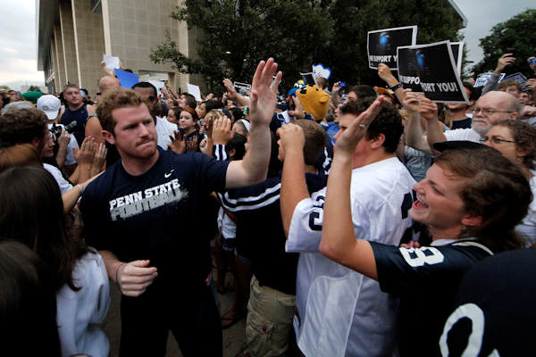 Penn State University quarterback Matt McGloin, left, and his teammates are greeted by a pep rally of supporters on the way to a morning workout outside the Lasch Football building on the Penn State main campus Tuesday, July 31, 2012. (AP Photo/Gene J. Puskar)