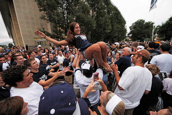 Penn State University freshman Shannon DaRin from Syracuse, NY, is tossed in the air during an early morning pep rally in support of the Penn State football team outside the Lasch Football Building on main campus before the team's morning workout Tuesday, July 31, 2012 in State College, Pa. (AP Photo/Gene J. Puskar)