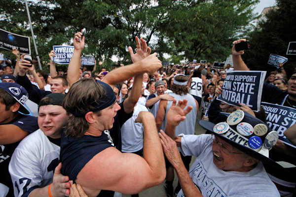 "<div class=""meta ""><span class=""caption-text "">Penn State University linebacker Michael Mauti, second from left foreground, and his teammates are greeted by a pep rally of supporters on the way to a morning workout outside the Lasch Football building on the Penn State main campus in State College, Pa., Tuesday, July 31, 2012. (AP Photo/Gene J. Puskar)</span></div>"