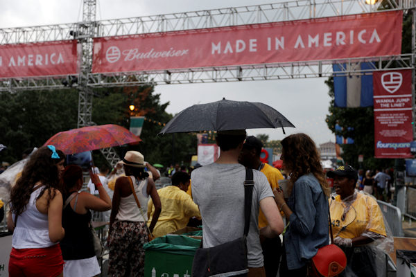 "Event goers with umbrellas in hand, shield themselves from a midday rainstorm go through security, for the ""Made In America"" music festival, on the Benjamin Franklin Parkway, Sunday, Sept. 2, 2012, in Philadelphia. (AP Photo/Matt Rourke)"
