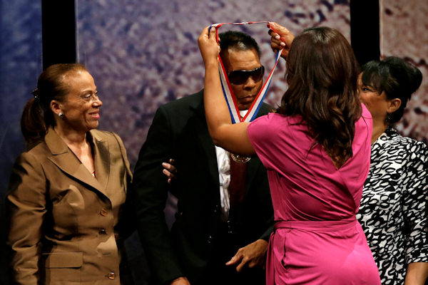 Retired boxing champion Muhammad Ali, center, is presented with the Liberty Medal by his daughter Laila Ali, right, as his wife Lonnie Ali, left, looks on during a ceremony at the National Constitution Center, Thursday, Sept. 13, 2012, in Philadelphia. The honor is given annually to an individual who displays courage and conviction while striving to secure liberty for people worldwide. His sister-in-law Marilyn Williams is at right. (AP Photo/Matt Slocum)