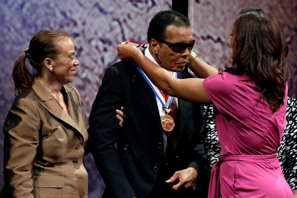Retired boxing champion Muhammad Ali, center, receives the Liberty Medal with his wife Lonnie Ali at his left during a ceremony at the National Constitution Center, Thursday, Sept. 13, 2012, in Philadelphia. The honor is given annually to an individual who displays courage and conviction while striving to secure liberty for people worldwide. (AP Photo/Matt Rourke)
