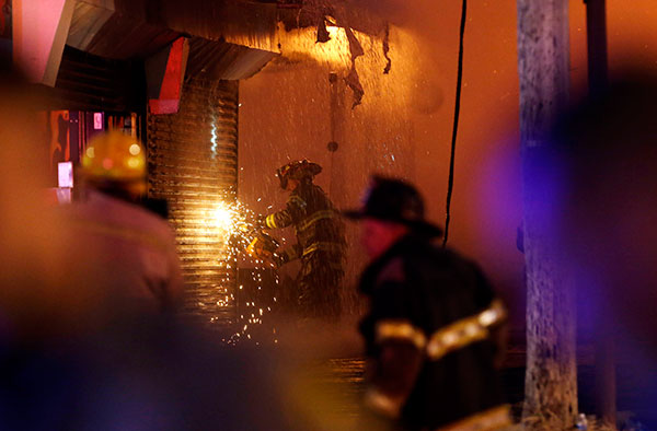 A firefighter saws through a metal wall on a building while battling a fire at the Seaside Park boardwalk on Thursday, Sept. 12, 2013, in Seaside Park, N.J. The fire began in a frozen custard stand on the Seaside Park section of the boardwalk and quickly spread north into neighboring Seaside Heights.  <span class=meta>(AP Photo&#47;Julio Cortez)</span>