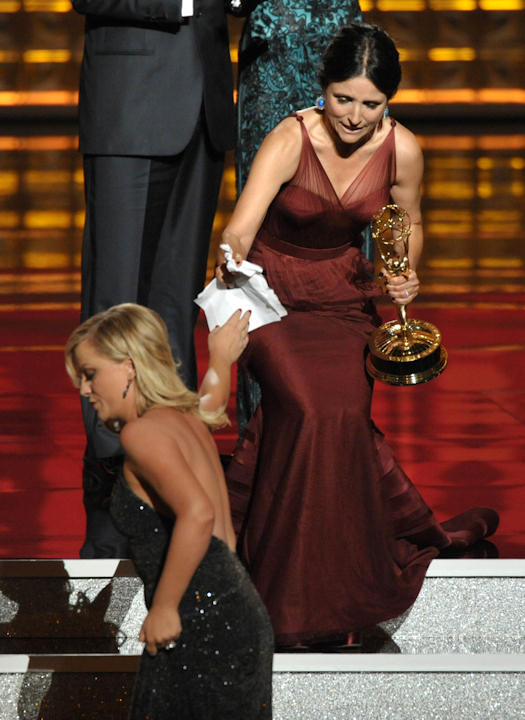 "Amy Poehler, left, hands Julia Louis-Dreyfus a piece of paper as Dreyfus accepts the award for Outstanding Lead Actress in a Comedy Series for ""Veep"" at the 64th Primetime Emmy Awards at the Nokia Theatre on Sunday, Sept. 23, 2012, in Los Angeles. (Photo by John Shearer/Invision/AP)"