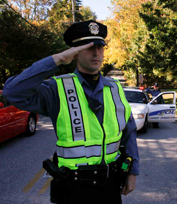 A police officer salutes the funeral procession for former U.S. Sen. Arlen Specter travels through Huntingdon Valley Pa., Tuesday Oct. 16, 2012, as it travels to Shalom Memorial Park for an internment service. Family members say Specter died Sunday of complications from non-Hodgkin's lymphoma. He was 82. (AP Photo/ Joseph Kaczmarek)