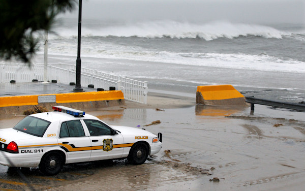 A police officer watches from his patrol car as the rough Atlantic Ocean threatens streets Monday Oct. 29, 2012, in Cape May, N.J., as Hurricane Sandy continues toward landfall. (AP Photo/Mel Evans)