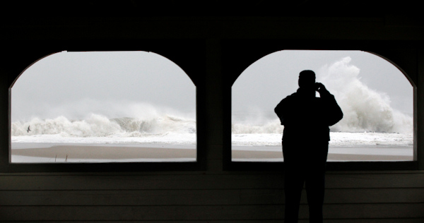 A person takes a photograph of the rough Atlantic Ocean from a pavalion in Cape May, N.J., Monday Oct. 29, 2012. Hurricane Sandy continued on its path Monday, as the storm forced the shutdown of mass transit, schools and financial markets, sending coastal residents fleeing, and threatening a dangerous mix of high winds and soaking rain. (AP Photo/Mel Evans)