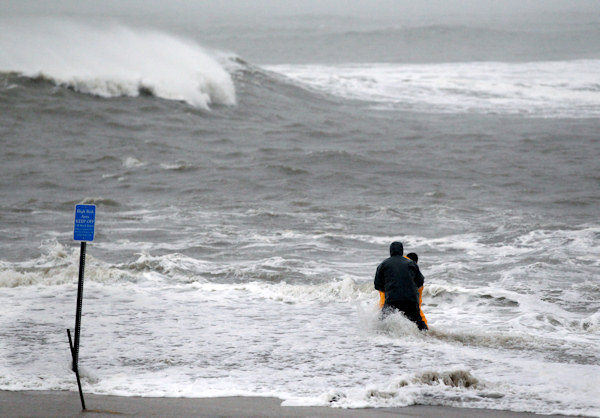 "<div class=""meta ""><span class=""caption-text "">Two men wade in the rough Atlantic Ocean Monday Oct. 29, 2012, in Cape May, N.J., as Hurricane Sandy continues toward landfall. Hurricane Sandy continued on its path Monday, as the storm forced the shutdown of mass transit, schools and financial markets, sending coastal residents fleeing, and threatening a dangerous mix of high winds and soaking rain. (AP Photo/Mel Evans)  </span></div>"