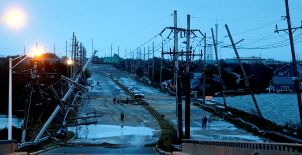"<div class=""meta ""><span class=""caption-text "">Downed power lines and a battered road is what superstorm Sandy left behind as people walk off the flooded Seaside Heights island, Tuesday, Oct. 30, 2012. Sandy, the storm that made landfall Monday, caused multiple fatalities, halted mass transit and cut power to more than 6 million homes and businesses.  (AP Photo/Julio Cortez)</span></div>"