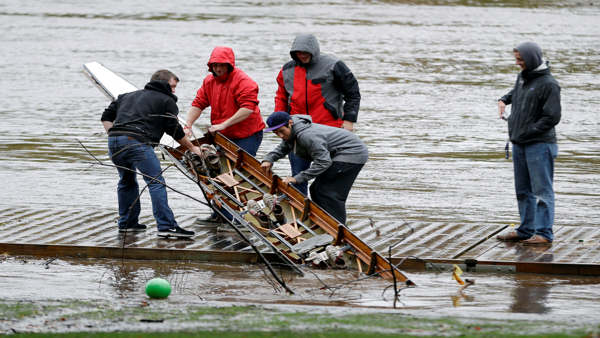 Members of the Saint Joseph&#39;s University crew team pull a damaged boat from the Schuylkill river in the wake of superstorm Sandy, Tuesday, Oct. 30, 2012, in Philadelphia. A one-two punch of rain and high wind from a monster hybrid storm that started out as a hurricane battered Pennsylvania, leaving more than a million customers without power as officials began assessing the damage Tuesday.  <span class=meta>(AP Photo&#47;Matt Slocum)</span>
