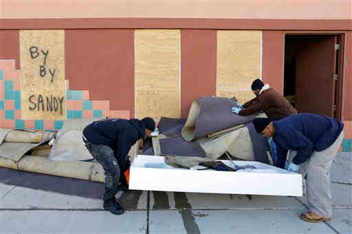 "<div class=""meta ""><span class=""caption-text "">Gordon Williams, left, Keith Downing, front right, and Daron Brown clean out a furniture store that was flooded by surge from superstorm Sandy in Atlantic City, N.J., Thursday, Nov. 1, 2012. (AP Photo/Patrick Semansky)</span></div>"