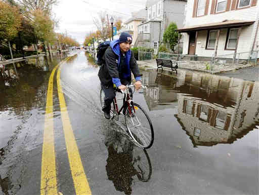 A man rides his bike through a flooded street in the wake of superstorm Sandy on Thursday, Nov. 1, 2012, in Little Ferry, N.J. Surprise coastal surge floods caused by the storm battered Little Ferry, Moonachie and some other towns along the Hackensack River in Bergen County _ all areas unaccustomed to flooding. (AP Photo/Mike Groll)