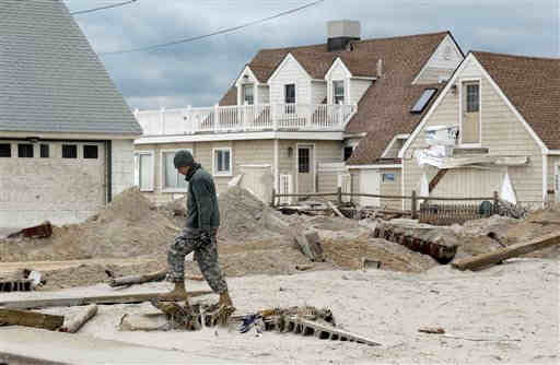 Pfc. Kyle Abbott, with the New Jersey National Guard, walks past houses that were damaged by superstorm Sandy in Brant Beach, N.J., Thursday, Nov. 1, 2012. In its tear of destruction, the megastorm Sandy left parts of New Jersey's beloved shore in tatters, sweeping away beaches, homes, boardwalks and amusement parks. (AP Photo/Patrick Semansky)