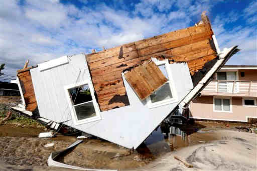 Part of a home rests upside-down in Seaside Heights, N.J. on Wednesday, Oct. 31, 2012 after superstorm Sandy made landfall in New Jersey on Monday evening. The rest of the home sat away from its original spot an in the middle of a street. (AP Photo/Julio Cortez)
