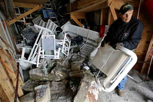 Robert Subranni carries furniture out of his garage that was flooded by surge from superstorm Sandy in Longport, N.J., Friday, Nov. 2, 2012. Four days after Sandy lashed the East Coast with high winds and a huge storm surge, frustration mounted, as millions of people remained without power and motorists lined up for hours at gas stations in New Jersey and New York. (AP Photo/Patrick Semansky)