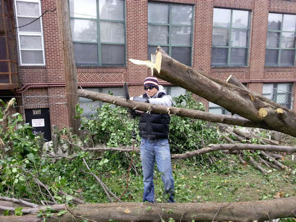 Adam Joseph removes a tree that fell in his neighbor's backyard during Hurricane Sandy.