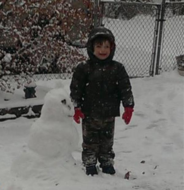 Miles Adams of Newportville, Pa. poses with the snowman he made with his poppy.
