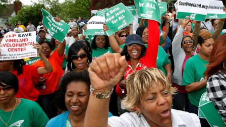 FILE - In this April 26, 2011 file photo, worker Marion Gaines, front right, reacts with others in a large gathering of