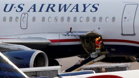 In this July 19, 2011 photo, baggage is unloaded from a U.S. Airways jet at Logan International Airport in Boston. US Airways Group Inc. said Thursday, July 21, its second-quarter profit fell 67 percent as fuel prices jumped. (AP Photo/Elise Amendola)