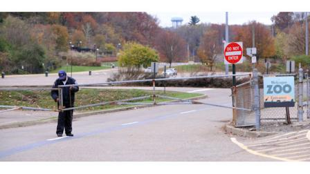 A security guard closes the gate at the Pittsburgh Zoo, where zoo officials say a young boy was killed after he fell into the exhibit that was home to a pack of African painted dogs, who pounced on the boy and mauled him, Sunday, Nov. 4, 2012. Its not clear whether he died from the fall or the attack, said Barbara Baker, president and CEO of the Pittsburgh Zoo and PPG Aquarium. (AP Photo/John Heller)