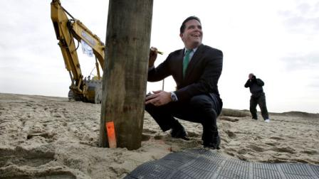 Belmar Mayor Matt Doherty signs the first piling of the new boardwalk construction Wednesday, Jan. 9, 2013, in Belmar, N.J. Belmar began construction on a 1.3-mile boardwalk to replace the walkway destroyed by Superstorm Sandy in October. The goal is to have it done by May. Doherty says new designs including the use of strong hurricane tie-down straps will help anchor the new boardwalk to its support moorings. The town intended to rebuild the boardwalk with tropical rain forest wood but abandoned those plans Tuesday, saying it wanted to avoid a protracted legal battle with environmentalists. (AP Photo/Mel Evans)