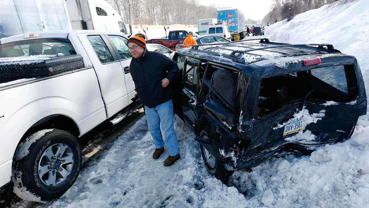 A man gets out of a SUV, one of many vehicles piled up in an accident, Friday, Feb. 14, 2014, in Bensalem, Pa. Traffic accidents involving multiple tractor trailers and dozens of cars have completely blocked one side of the Pennsylvania Turnpike outside Philadelphia and caused some injuries. Matt Rourke/AP