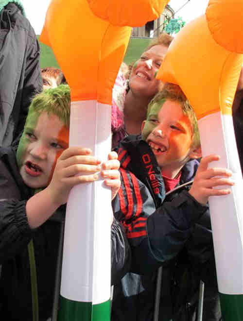 Two boys wield toy hammers the color of the Irish flag as they cheer the passing St. Patrick's Day parade in Dublin, Saturday, March 17, 2012. Police estimate a half-million spectators lined the route of the parade, the biggest of more than 50 across Ireland. (AP Photo/Shawn Pogatchnik)