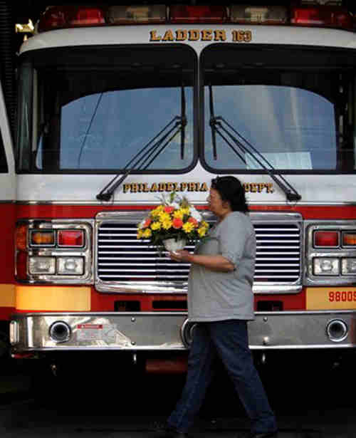 A visitor carries flowers to a memorial for fallen firefighters Lt. Robert Neary, 60, and firefighter Daniel Sweeney, 25, outside the Ladder Company 10 firehouse in Philadelphia, on Monday April 9, 2012. Two firefighters who were battling a massive blaze at an abandoned warehouse Monday were killed when an adjacent furniture store they were inspecting collapsed, burying them in a pile of debris, authorities said. (AP Photo/Joseph Kaczmarek)