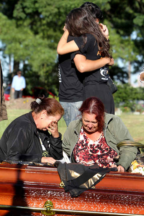 "<div class=""meta ""><span class=""caption-text "">Relatives and friends mourn next to the coffin during the burial of fire victim Tanise Cielo, at a cemetery in Santa Maria city, Rio Grande do Sul state, Brazil, Monday, Jan. 28, 2013. A fast-moving fire roared through the crowded, windowless Kiss nightclub in southern Brazil early Sunday, within seconds filling the space with flames and a thick, toxic smoke that killed more than 230 panicked partygoers who gasped for breath and fought in a stampede to escape. (AP Photo/Nabor Goulart)</span></div>"