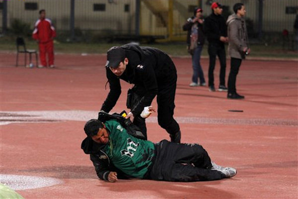 An Egyptian policeman helps an injured soccer fan during clashes at the football stadium in Port Said, Egypt Wednesday, Feb. 1, 2012.  <span class=meta>(AP Photo)</span>