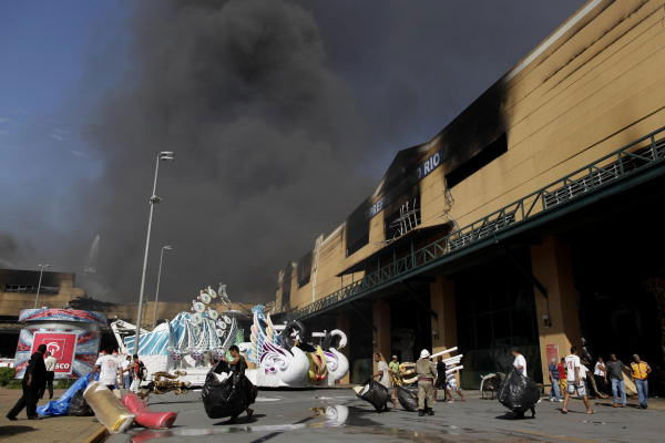 "<div class=""meta ""><span class=""caption-text "">Firefighters try to extinguish a fire as people remove costumes and props for Carnival from a warehouse, in Samba City, Rio de Janeiro, Brazil, Monday, Feb. 7, 2011. Amassive fire is consuming the warehouses where Rio de Janeiro's samba groups store the props and costumes for Brazil's largest Carnival parade.  ((AP Photo/Felipe Dana))</span></div>"