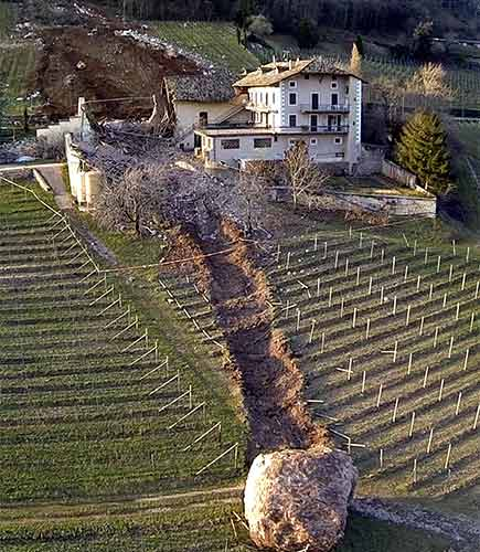 In this photo provided by Tareom.com Thursday, Jan. 30, 2014, and taken on Jan. 23, 2014, a huge boulder is seen after it stopped next to a farm house, while a second giant boulder, which detached during the same landslide on Jan. 21, 2014, whose trail can be seen at right, missed the house by less than a meter, destroying the barn, and stopped in the vineyard below, in Ronchi di Termeno, in Northern Italy. According to reports, the Trebo family living there was unharmed in the landslide.  <span class=meta>(AP Photo&#47;Markus Hell, Tareom.com, ho)</span>