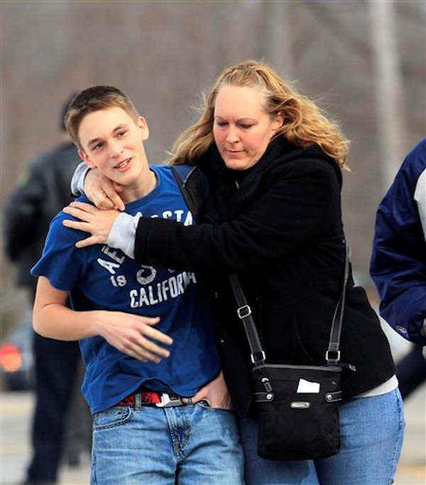 Doug Gasper, a ninth grader at Chardon High School, is hugged by his mother, Sandy, as they leave Maple Elementary School Monday, Feb. 27, 2012, in Chardon, Ohio.  <span class=meta>(AP Photo&#47;Tony Dejak)</span>