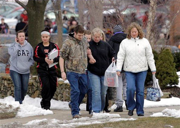 Parents walk past Chardon Middle School with students in Chardon, Ohio Monday, Feb. 27, 2012.  <span class=meta>(AP Photo&#47;Mark Duncan)</span>