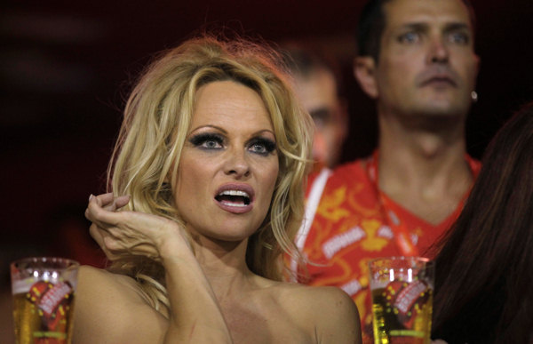 Pamela Anderson gestures from the stands as she watches a carnival parade at the Sambadrome in Rio de Janeiro, Brazil, Sunday March 6, 2011.  <span class=meta>(AP Photo&#47;Silvia Izquierdo)</span>