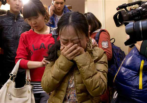 A Chinese relative of passengers aboard a missing Malaysia Airlines plane, center, cries as she is escorted by a woman while leaving a hotel room for relatives or friends of passengers aboard the missing airplane, in Beijing, China Sunday, March 9, 2014. Planes and ships from across Asia resumed the hunt Sunday for the Malaysian jetliner missing with 239 people on board for more than 24 hours, while Malaysian aviation authorities investigated how two passengers were apparently able to get on the aircraft using stolen passports. &#40;AP Photo&#47;Andy Wong&#41; <span class=meta>(Photo&#47;Andy Wong)</span>