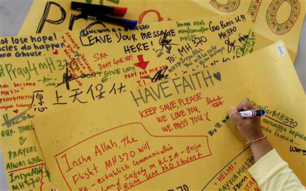 A woman writes a wishing message on a cardboard at Kuala Lumpur International Airport in Sepang, Malaysia, Monday, March 10, 2014. Vietnamese aircraft spotted what they suspected was one of the doors of the missing Boeing 777 on Sunday, while questions emerged about how two passengers managed to board the ill-fated aircraft using stolen passports. &#40;AP Photo&#47;Daniel Chan&#41; <span class=meta>(Photo&#47;Daniel Chan)</span>