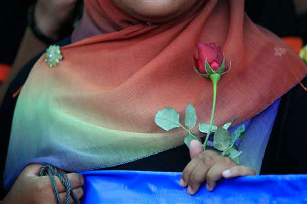 "<div class=""meta image-caption""><div class=""origin-logo origin-image ""><span></span></div><span class=""caption-text"">A member of a youth group holds a rose as she prays for the missing Malaysia Airlines plane outside a hotel in Putrajaya, Malaysia, Monday, March 10, 2014. Vietnamese aircraft spotted what they suspected was one of the doors of the missing Boeing 777 on Sunday, while questions emerged about how two passengers managed to board the ill-fated aircraft using stolen passports. (AP Photo/Lai Seng Sin) (Photo/Lai Seng Sin)</span></div>"